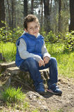 The green-eyed boy sitting in the woods. Royalty Free Stock Photos