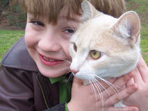Green eyed cat and boy. Portrait of cream colored green-eyed cat with young boy in green field Stock Images