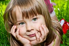 Green-eyed charming little girl lying in a grass Stock Image