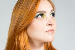 Green-eyed girl looks up. Redheaded girl wearing colorful yellow. Green-eyed girl is looking upwards and with interested look. Fashion and colorful makeup Stock Image