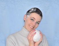 Green-eyed girl with snowflakes and snowball smi Stock Photos