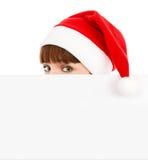 Green-eyed Santawoman peeking over blank billboard stock photos