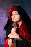 Green eyed sorceress. Vampire gothic woman or sorceress with green eyes and a sword stock photo