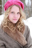 Green Eyed Winter Woman Portrait. Portrait of a slightly smiling, wholesome, beautiful, green eyed young woman wearing a fur jacket and pink beret in a snowy Stock Photography