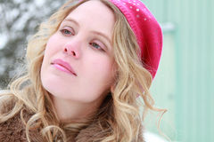 Green Eyed Winter Woman Portrait. Portrait of a slightly smiling, wholesome, beautiful, green eyed young woman wearing a fur jacket and pink beret with snowy Stock Photography