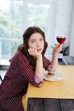 Green-eyed woman feeling awful being alone on her birthday. Alone on birthday. Green-eyed woman wearing nice striped dress feeling extremely awful being alone on stock images