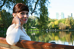 Green eyed woman talking on the phone. In the park Royalty Free Stock Photo