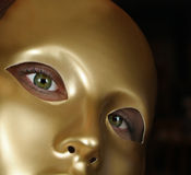 Green Eyes and Gold Mask. Woman with beautiful green eyes wearing gold mask stock images