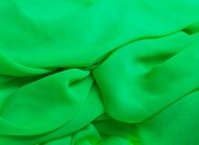 Green fabric. Bright green fabric. The beautiful fashion background Stock Photography