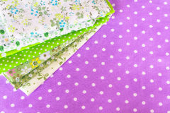 Green fabric on purple background. Cloth set. Sewing supplies. Sewing materials. Sewing needlework concept Royalty Free Stock Photo