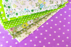 Green fabric on purple background. Sewing fabric kit. Sewing fabric supplies Royalty Free Stock Image