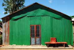 Green facade house. Abstract facade house with iron wall, green metal sheet make nice exterior of home, bench red door in lock and bench in front of house stock photos