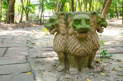 Green face three headed sandstone lion sculpture stay alone in a public park. royalty free stock photos