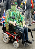 Green faced men on wheelchair. Green face man sits on his wheelchair during the parade of traditional Jack in the Green Festival in Hastings UK Stock Image
