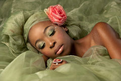 Green fairy fantasy woman. Beautiful african woman in green fantasy makeup lying in green organza fabric with pink roses looking down at her pink ring Stock Photos