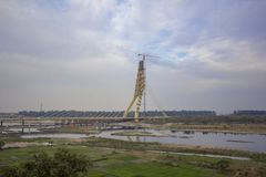 Green farm fields near a cable-stayed bridge under construction and a tower crane over the Yamuna River against a blue sky. A green farm fields near a cable royalty free stock images