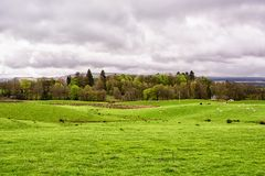 Green farm fields under a cloudy sky in Scotland, United Kingdom. Spring time Royalty Free Stock Image