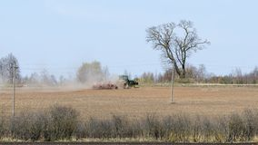 Green farm tractor cultivate the field. At spring royalty free stock photography