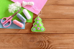 Green felt Christmas tree with pink and blue balls, thread, scissors, needle, felt sheets on a wooden table with empty space Royalty Free Stock Photo