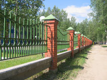Green fence with brick column. In summer day Royalty Free Stock Photography