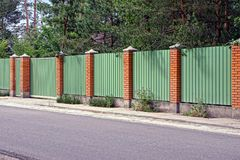 Green fence and gates in front of the asphalt road Royalty Free Stock Photo