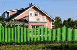 The green fence next to the country house pink. Green fence in front of a wooden house Royalty Free Stock Image