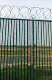 Green fence with razor wire guarding French ferry terminal. Stock Image