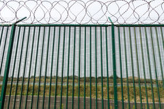 Green fence with razor wire guarding French ferry terminal. Royalty Free Stock Photography