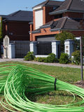 Green fiber optic cable piled in front of residential housing Royalty Free Stock Photos