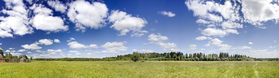 Green field. Panoramic photo of spring landscape with blue sky Stock Photos