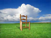 Green field. Wood chair on a grass field Royalty Free Stock Image