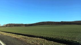 Green field against hills with trees in early spring. View from moving car window. stock video
