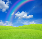 Green field with blue sky. And rainbow Stock Photos