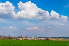Green field and blue sky with clouds. Rural landscape stock photography
