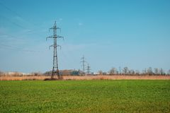 Green field and blue sky, in the distance power lines with many wires. Electrical tower with wires stock images