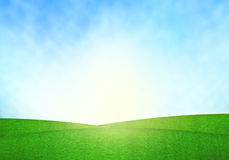 Green field, blue sky and lighting flare on grass. Royalty Free Stock Image