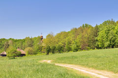 Green field, blue sky and old wooden chapel Royalty Free Stock Images