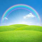 Green field with blue sky and rainbow Royalty Free Stock Image