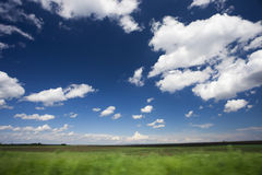 Green field and clouds Stock Image