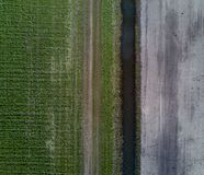 Green field and dirt field separate by small water cannal. royalty free stock photography