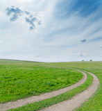 Green field with dirty road Royalty Free Stock Image