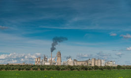 Green Field And Factory With Dark Smoke Coming Out Of Chimney Stock Photography