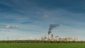 Green Field And Factory With Dark Smoke Coming Out Of Chimney Stock Images