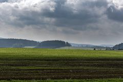 Green field in the foreground forests on the hills under dark clouds Royalty Free Stock Image