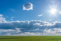 Green field with fresh vibrant grass and blue sky with dramatic clouds and the sun at the daytime Stock Photo