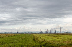 Green field in front of industrial oil plant. A green field sitting in front of an industrial oil refinery in gloomy weather stock image