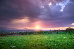 Green field and heavy clouds at sunset Royalty Free Stock Images