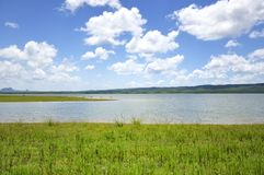 Green field, lake and sky background Royalty Free Stock Photos