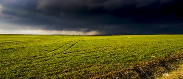 A green field laying under cloudy dark sky stock photography