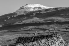 Snow capped mountain with farm land in black and white stock image